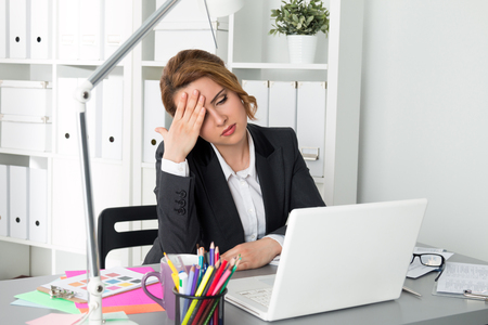 overworking: Portrait of tired businesswoman sitting at her office and touching her head. Woman trying to concentrate. Headache, problems, stress at work, overworking or deadline concept