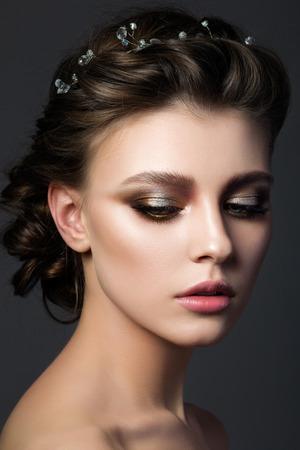 ブライダルのメイクや髪形を持つ若い美しい女性の肖像画。モダンなスモーキー目を占めています。スタジオ撮影します。メイクアップ サロン 写真素材