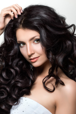 hair and beauty: Portrait of young beautiful woman with luxuriant black hair. Haircare or beauty salon concept. Wedding makeup and coiffure. Studio shot Stock Photo
