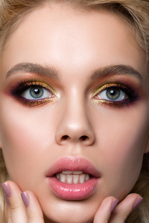 unexpectedness: Close-up portrait of young surprised woman touching her face. Girl with open mouth. Unexpected news or sale concept. Modern fashion multicolored smokey eyes make-up.