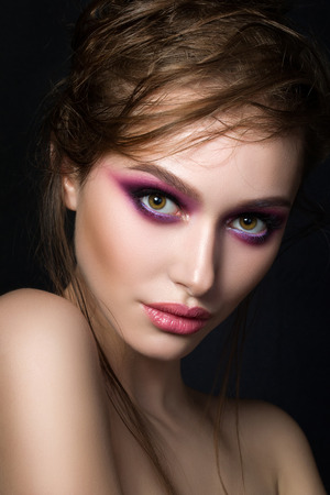 Closeup portrait of young beautiful woman with bright pink smokey eyes and lips over black background. Fashion makeup. Studio shot. Modern spring or summer make up