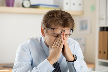 overworking: Tired office worker touching his bridge of nose to give rest to eyes and concentrate. Accountant making financial report. Deadline and overworking concept.