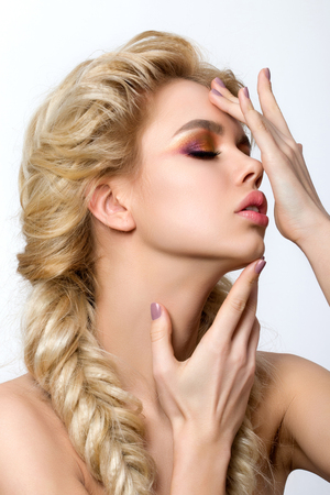 french model: Portrait of young beautiful blonde woman with creative make-up and french braids touching her face. Multicolored smokey eyes. Modern makeup, hairdressing or skincare concept