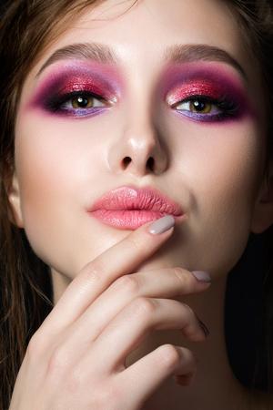 Retrato de mujer joven y bella con los ojos brillantes de color rosa ahumados y labios. Maquillaje de la manera. estudio de disparo. verano constituyen modernos