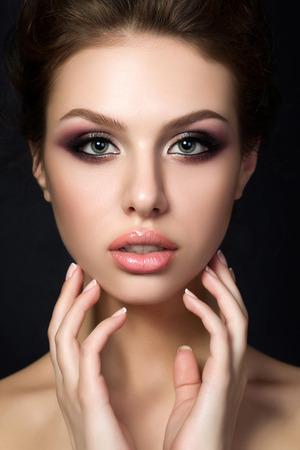 夜の若い美しい女性の肖像画は、黒背景に彼女の顔に触れることを確認します。色とりどりのスモーキーな目。高級スキンケアと現代ファッション