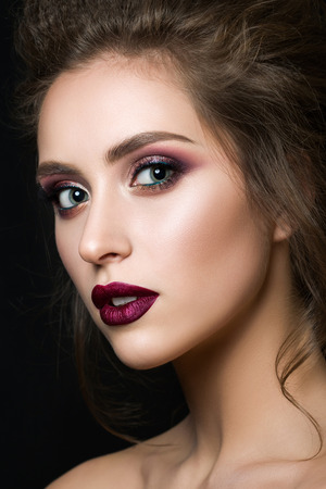 Portrait of young beautiful woman with evening make up over black background. Multicolored smokey eyes and dark red velvet mat lips. Luxury skincare and modern fashion makeup concept. Studio shot. Stock Photo