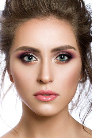 Closeup portrait of young beautiful woman with modern multicolored smokey eyes make up. Face skincare and fashion make-up concept. Studio shot.