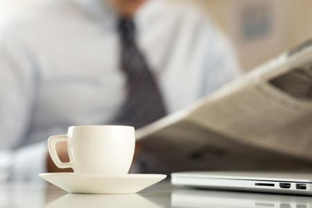cuadro sinoptico: Taza de café de la mañana en la mesa de trabajo con retención analista de negocios en las manos y leer el periódico en el fondo. cotización en la bolsa, se relaja en el lugar de trabajo o resultado del partido de fútbol concepto Foto de archivo