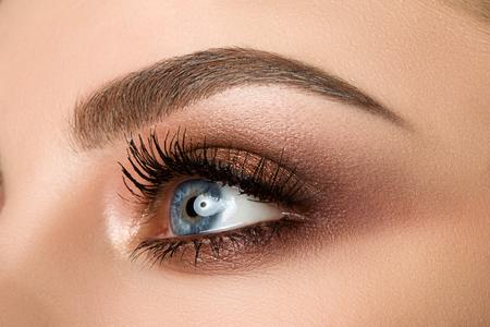 Schließen Sie oben von blauem Frauenauge mit schönem Braun mit Rot- und Orangetönen rauchigen Augen Make-up. Moderne Mode schminken. Standard-Bild