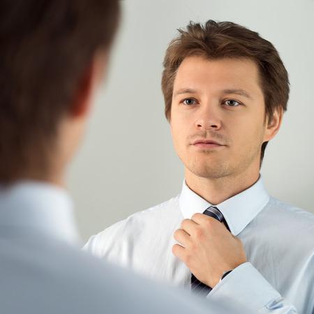 Apuesto hombre de negocios que se prepara para evento oficial, enderezar corbata. Nueva entrevista de trabajo, auto-motivación para la confianza, tratando nudo de la corbata de moda, el concepto de servicio a medida
