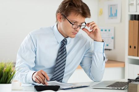 Portrait de comptable ou de l'inspecteur financier ajustant ses lunettes faisant rapport, de calcul ou de contrôle d'équilibre. Accueil finances, l'investissement, l'économie, les économies d'argent ou d'un concept d'assurance Banque d'images - 56057670
