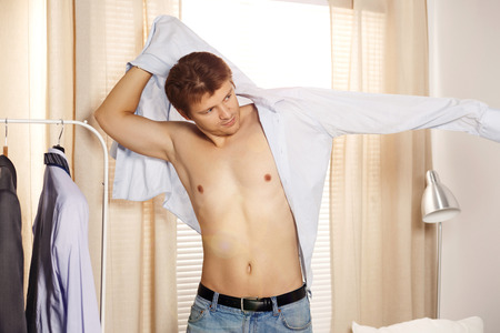successful man: Handsome man putting on shirt standing near window at his room in morning. Preparing for some event or new workday. New opportunities, dating, wedding day or getting ready for job interview concept Stock Photo