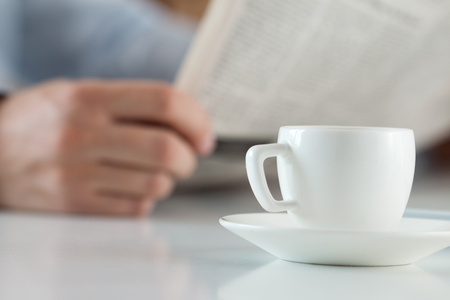 cuadro sinoptico: Taza de café de la mañana en la mesa de trabajo con retención analista de negocios en las manos y leer el periódico en el fondo. cotización en la bolsa, se relaja en el lugar de trabajo, o el concepto de resultado del partido de fútbol Foto de archivo