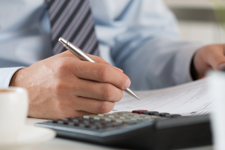Close up of male accountant making calculations. Man writing something sitting at his office. Partnership agreement, contact signing, closing balance, making financial report or economy concept