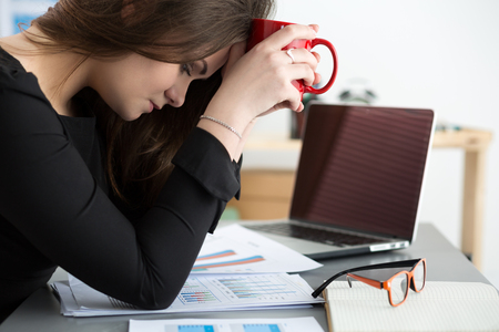 overworking: Tired female employee at workplace in office holding cup of tea. Sleepy worker early in the morning after late night work. Overworking, making mistake, stress, termination or depression concept