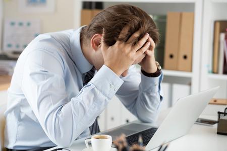 Müde Geschäftsmann am Arbeitsplatz im Büro hält seinen Kopf in den Händen. Sleepy Arbeiter früh am Morgen nach dem Ende der Nachtarbeit. Überarbeitung, so dass Fehler, Stress, Beendigung oder Depression Konzept