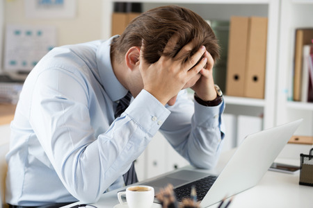 Tired business man at workplace in office holding his head in hands. Sleepy worker early in the morning after late night work. Overworking, making mistake, stress, termination or depression concept
