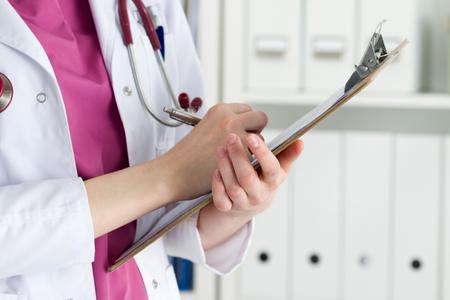 Sluit omhoog mening van vrouwelijke artsenhanden houdend het knippen stootkussen en het schrijven geduldige geschiedenis of het voorschrijven van sommige geneesmiddelen. Gezondheidszorg en medisch concept.