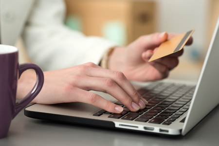 online purchase: Close up view of businesswoman hands holding credit card and making online purchase using notebook pc. Shopping, consumerism, delivery, financial security, anti-fraud or internet banking concept.