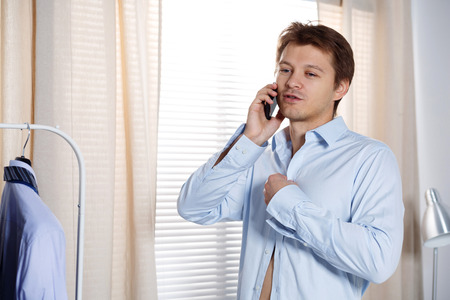 hasten: Portrait of busy young man putting on his shirt and talking on phone. Broker, agent or sales manager hasten to work. Hurry to important meeting or office. Support concept