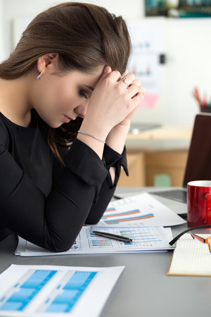 overworking: Tired female employee at workplace in office touching her head. Sleepy worker early in the morning after late night work. Overworking, making mistake, stress, termination or depression concept
