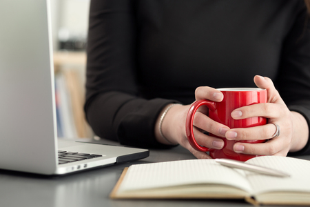 hard day at the office: Female designers in office drinking morning tea or coffee. Coffeebreak during hard working day. Girl holding cup of hot beverage.