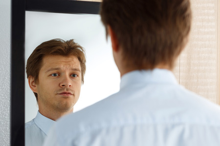 looking for job: Portrait of unsure young businessman with unhappy face looking at the mirror. Man preparing for important meeting, new job interview or dating. Difficult relationship, stress management concept Stock Photo