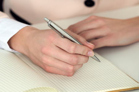 self exam: Woman hand holding silver pen ready to make note in opened notebook. Businesswoman or employee at workplace writing business ideas, plans, tasks at personal organizer. Office life or education concept Stock Photo