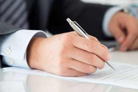 financial insurance: Close-up of businessman hands signing documents. Man writing something sitting at his office. Partnership agreement of contact signing, closing balance or making financial report concept