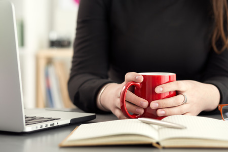 blogs: Female designer in office drinking morning tea or coffee. Coffeebreak during hard working day. Girl holding cup of hot beverage.