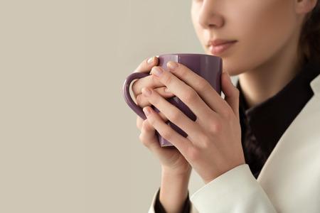 コーヒーや紅茶のカップを保持している若くてきれいな女性の手のクローズ アップ。朝のコーヒー、寒い季節、オフィス コーヒー ブレークやコー
