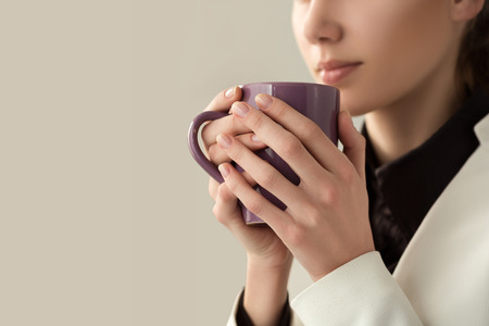 Close up of young beautiful woman hands holding hot cup of coffee or tea. Morning coffee, cold season, office coffee break or coffee lover concept.