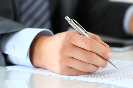 essays: Close up of businessman hands signing documents. Man writing something sitting at his office. Partnership agreement of contact signing, closing balance or making financial report concept