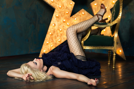 down lights: Beautiful playful adult blonde woman wearing dark blue lace skirt and mesh stockings posing over dark background with glowing star. Actress playing on stage. Theatre or dancer.