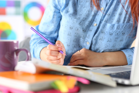 letter writing: Female student or designer at workplace holding pencil and writing or making sketches. Woman writing letter, list, plan, making notes, doing homework. Education or creative work concept