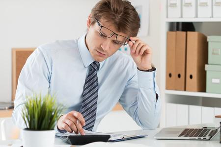 Portret van boekhouder of financieel inspecteur aanpassing van zijn bril het maken van rapport, het berekenen of het controleren balans. Thuis financiën, investeringen, economie, geld te besparen of verzekeringsconcept Stockfoto