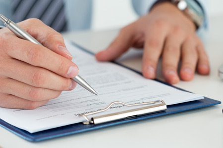 audits: Close up of male accountant making calculations. Man writing something sitting at his office. Filling individual income tax return form 1040, making financial report, home finances or economy concept