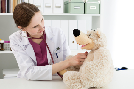 communicable: Family doctor examination. Beautiful smiling female doctor in white coat examine teddy bear with stethoscope to calm down and interest child. Playing with baby patient. Pediatrics medical concept Stock Photo