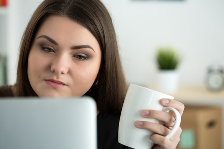 person reading: Portrait of young sad or attentive woman looking at laptop monitor and holding white cap of tea. Online education, coffee break or dieting concept