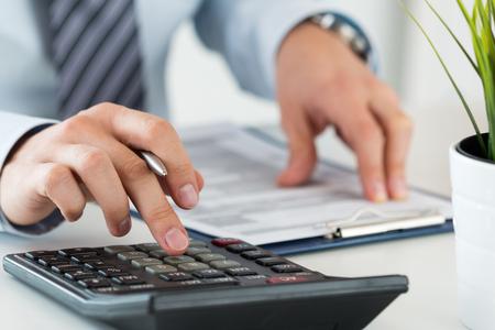Close-up van mannelijke accountant of bankier berekenen of het controleren balans. Boekhouder of financieel inspecteur maken van financieel verslag. Thuis financiën, investeringen, economie, geld te besparen of verzekeringsconcept