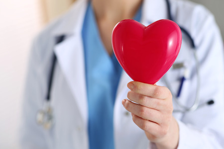 prophylaxis: Female medicine doctor hands holding red toy heart in front of her chest closeup. Medical help, cardiology care, health, prophylaxis, prevention, insurance, surgery and resuscitation concept