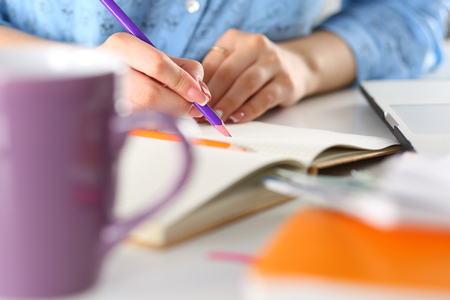 essay: Female student or designer at workplace holding pencil and writing or making sketches. Woman writing letter, list, plan, making notes, doing homework. Education or creative work concept