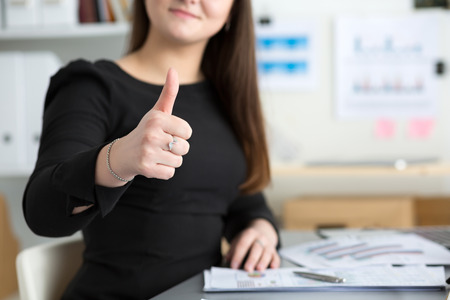 satisfied customer: Business woman shows thumb up sitting at her office closeup. Perfect goods or service quality concept. Satisfied customer. Okay symbol