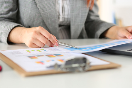 auditor: Businesswoman looking at graphics. Manager or auditor reading reports. Financial planning, business analysis and project management concept. Stock Photo