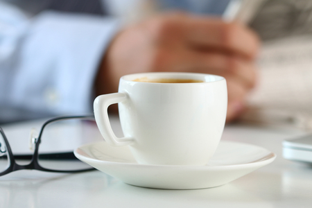 cuadro sinoptico: Cup of morning coffee on worktable with business analyst hold in hands and read newspaper on background. Price quotation on the exchange, relaxing at workplace or football match result concept