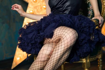 Hermosa mujer juguetona que lleva oscuros falda de encaje azul y medias de malla que presenta en silla sobre fondo oscuro con la estrella que brilla intensamente. Piernas de cerca. Actriz que interpreta en el escenario. Teatro o bailarina.