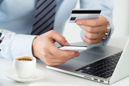 Close-up van zakenman handen bedrijf creditcard en het maken van online aankopen met behulp van de mobiele telefoon. Winkelen, consumentisme, levering, financiële zekerheid, anti-fraude of internet bankieren concept. Stockfoto