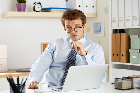 auditor: Portrait of bookkeeper or auditor sitting at his workplace. Businessman looking at camera sitting at his office. Stock Photo
