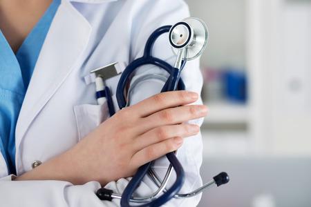 estetoscopio: Primer plano de doctor en medicina femenina terapeuta de pie con las manos cruzadas sobre el pecho sosteniendo el estetoscopio en la oficina. ayuda médica o concepto de seguro. Médico está esperando paciente a examinar