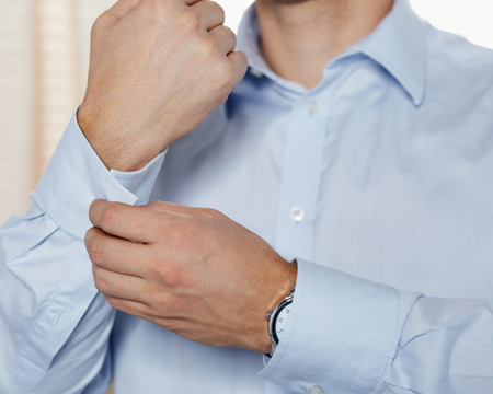 fastens: Man fastens his cuff links close-up. Businessman or fiance preparing himself for going out.